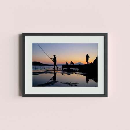 SARTI, GREECE - September 2019: Men fishing off the dock in Sarti, Greece.